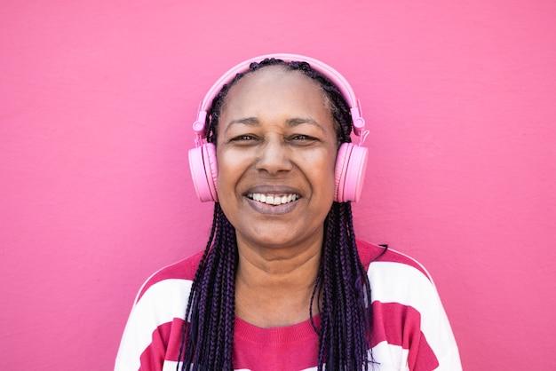 Mulher africana sênior ouvindo música de lista de reprodução com fones de ouvido - foco no rosto