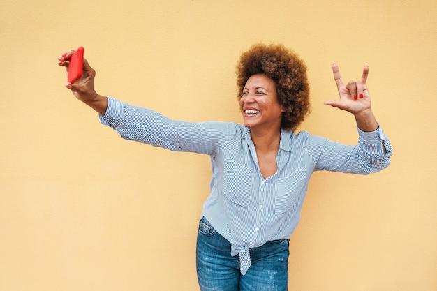 Mulher africana sênior usando aplicativo de smartphone enquanto tira uma foto de selfie