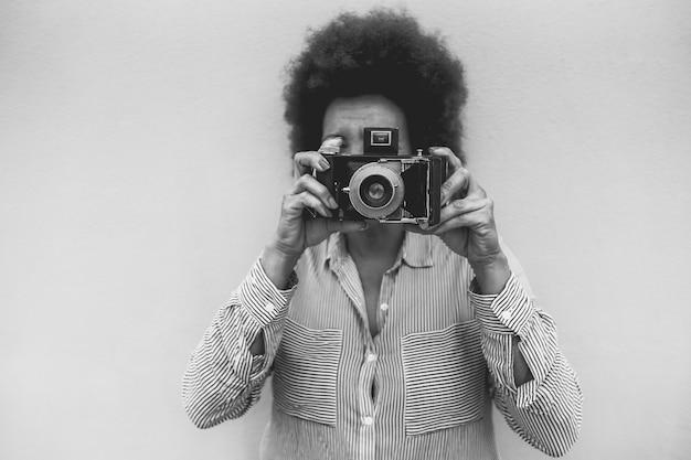 Mulher africana sênior usando câmera vintage ao ar livre na cidade - foco na lente