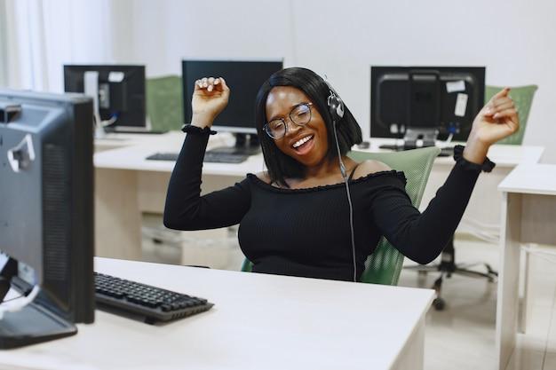 Mulher africana sentada na aula de ciência da computação. senhora de óculos. aluna sentada em frente ao computador.