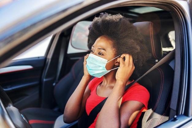 Mulher africana sentada no carro dela e colocando máscara no rosto. conceito de surto de covid-19.