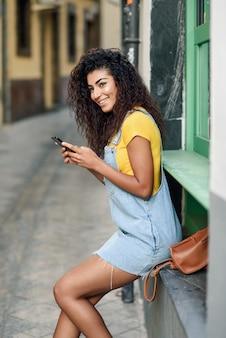 Mulher africana, sentando, ao ar livre, texting, com, dela, esperto, telefone