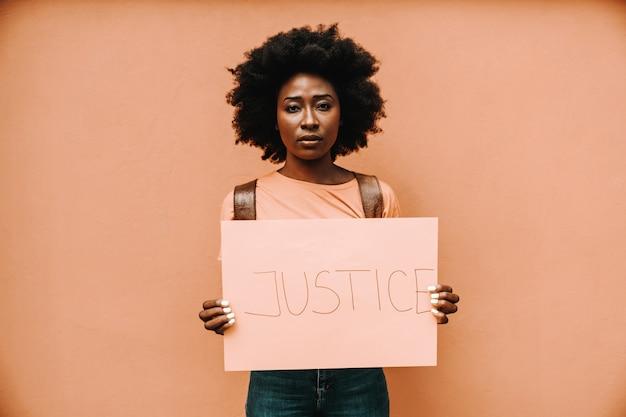 Mulher africana séria atraente em pé e segurando o papel com o título de justiça.