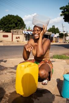 Mulher africana servindo água em um recipiente ao ar livre