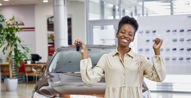 Mulher africana sorridente com as chaves de seu carro novo