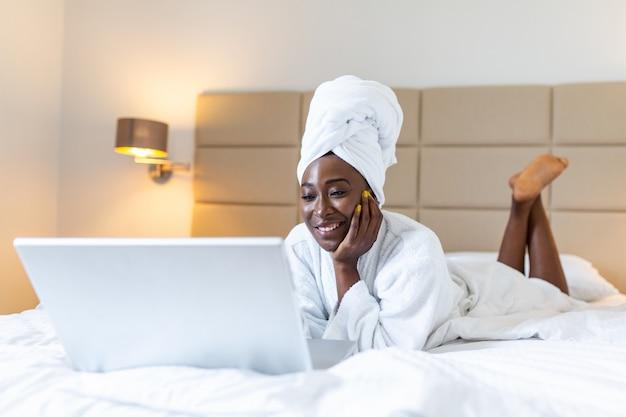 Mulher africana sorridente, deitada na cama em roupão com laptop navegando na internet.