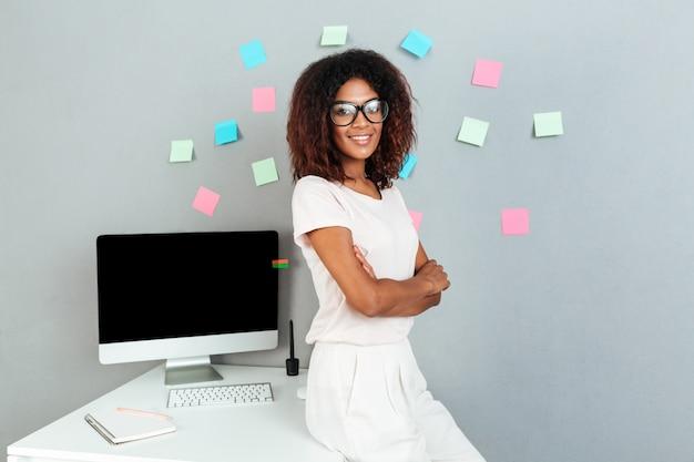 Mulher africana sorridente em óculos em pé perto da mesa