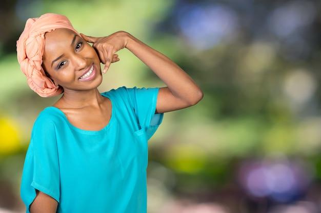 Mulher africana sorridente fazendo me chama de sinal