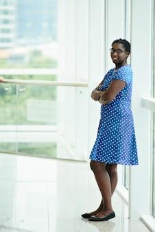 Mulher africana sorridente no vestido de bolinhas azuis, inclinando-se contra a moldura da janela e sorrindo