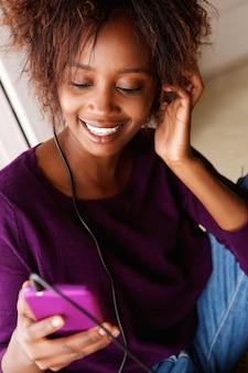 Mulher africana sorridente ouvindo música com telefone inteligente