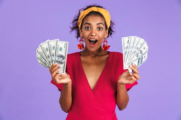 Mulher africana surpresa com vestido segurando dinheiro