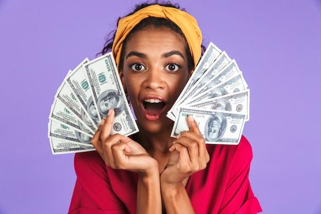 Mulher africana surpresa engraçada com vestido segurando dinheiro