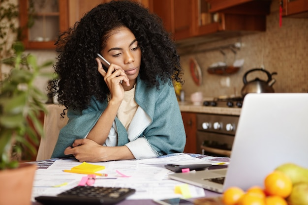 Mulher africana triste com penteado afro, sentada na cozinha em frente ao laptop, falando ao telefone celular com o marido, dizendo a ele que sua família será despejada em breve por falta de pagamento do aluguel