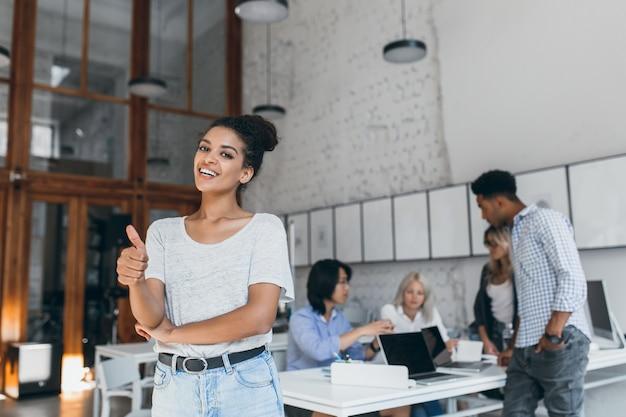 Mulher africana usa jeans azul claro e faixa preta, desfrutando do trabalho em equipe com colegas internacionais. especialistas freelance femininos elegantes posando enquanto seus amigos trabalham com o laptop.