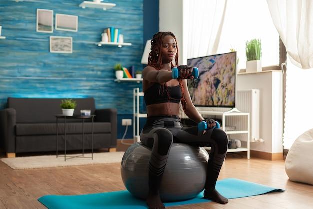 Mulher africana usando bola de estabilidade, mantendo os braços estendidos, exercitando os ombros com halteres azuis, na sala de estar de casa para modelagem muscular e estilo de vida saudável, vestida com roupas esportivas