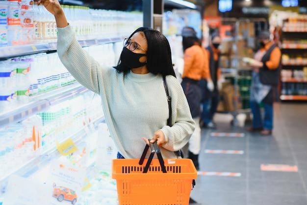 Mulher africana usando máscara médica descartável, compras no supermercado durante o surto de pandemia de coronavírus. época de epidemia.