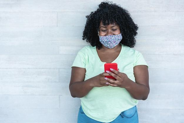 Mulher africana usando telefone celular enquanto usa máscara protetora