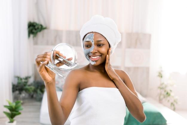 Mulher africana vestindo uma toalha e máscara facial na metade do rosto