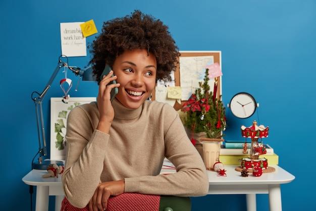 Mulher afro alegre sentada na cadeira, curtindo uma conversa agradável