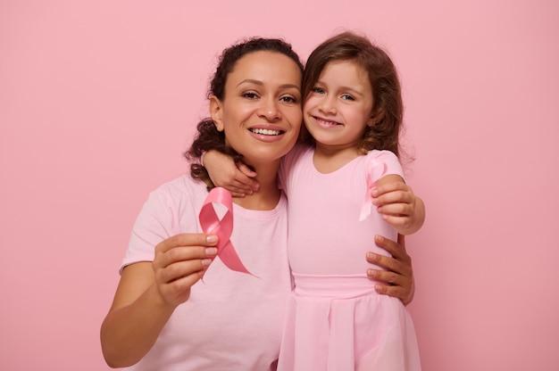 Mulher afro-americana abraça a filha dela, segurando uma fita rosa, sorrisos bonitos, olhando para a câmera, isolada em um fundo colorido com espaço de cópia. dia internacional da luta contra o câncer de mama
