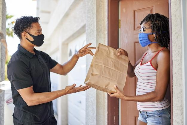 Mulher afro-americana abrindo porta para receber pedido de retirada enquanto usa máscara