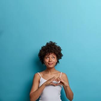 Mulher afro-americana afetuosa e romântica que expressa paixão e romance, faz gestos de coração, olha para cima, vestida com colete casual, isolada na parede azul, espaço em branco para sua promoção
