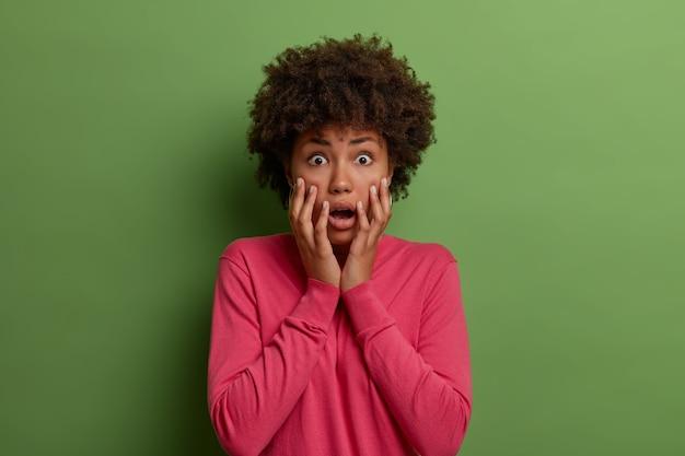 Mulher afro-americana alarmada e insegura encara ansiosa, sente-se chocada e envergonhada, mantém as palmas das mãos no rosto, usa um suéter rosa, percebe algo chocante isolado na parede verde.