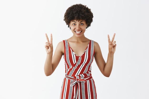 Mulher afro-americana alegre, bonita e simpática, de macacão listrado, mostrando sinais de v ou gesto de vitória e sorrindo amplamente, fazendo aspas no ar sobre a parede cinza