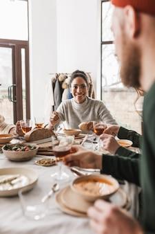 Mulher afro-americana alegre com cabelo escuro e encaracolado sentada à mesa tomando sopa com uma fatia de pão na mão com alegria.
