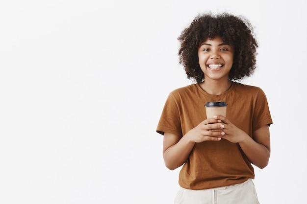 Mulher afro-americana alegre, despreocupada e amigável, com um penteado afro, segurando uma xícara de café com as duas mãos e sorrindo amplamente enquanto tem uma conversa interessante