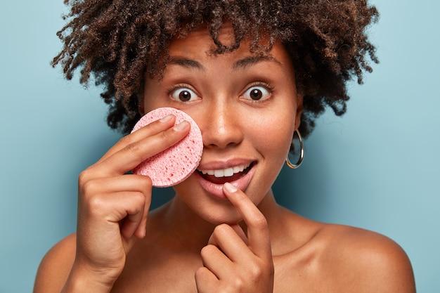 Mulher afro-americana alegre e surpresa ouve conselhos sobre como cuidar da pele, segura a esponja cosmética na bochecha, tem os olhos bem abertos, reação de choque, remove a maquiagem. conceito de spa e relaxamento