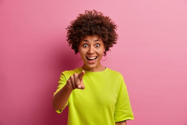 Mulher afro-americana alegre e surpresa vestida com roupas casuais aponta diretamente para você e escolhe algo chocou expressão alegre vestida casualmente isolada sobre a parede rosa do estúdio