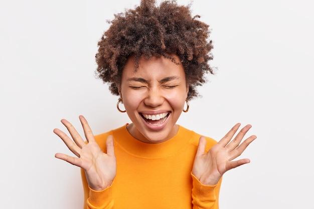 Mulher afro-americana alegre expressa sorrisos de felicidade amplamente mantém os olhos fechados levanta as palmas das mãos tem humor otimista envia vibrações positivas vestidas casualmente isoladas sobre uma parede branca. conceito de emoções