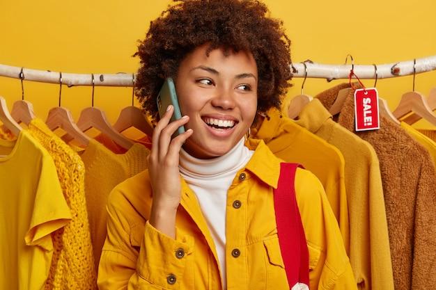 Mulher afro-americana alegre fala ao celular, dá uma olhada em algumas roupas na loja, posa sobre o cabideiro, divulga as vendas da loja