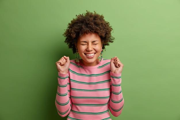 Mulher afro-americana alegre levanta os punhos antecipa que algo de bom aconteça fica radiante fecha os olhos com grande desejo de ouvir os resultados vestida com um macacão listrado casual isolado na parede verde
