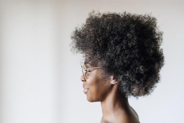 Mulher afro-americana alegre posando contra uma parede branca