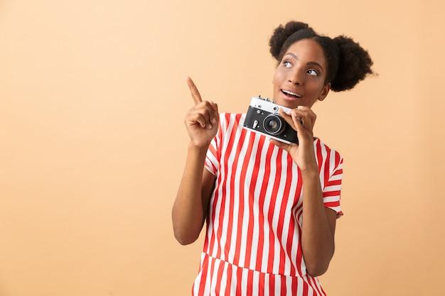 Mulher afro-americana alegre sorrindo e fotografando na câmera retro, isolada