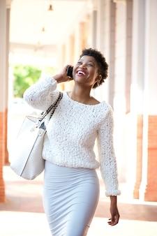 Mulher afro-americana andando e falando com o celular
