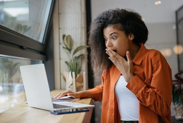 Mulher afro-americana animada olhando para a tela do laptop, lendo notícias chocantes on-line