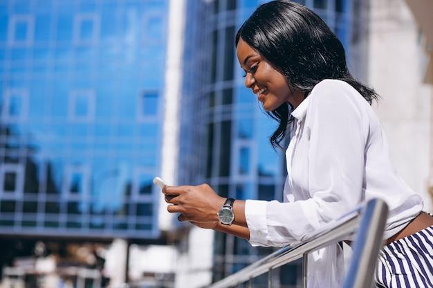 Mulher afro-americana ao ar livre pelo arranha-céu com telefone