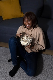 Mulher afro-americana assistindo serviço de streaming em casa