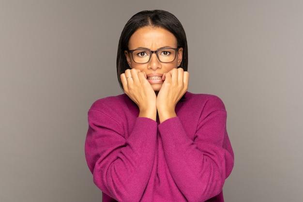 Mulher afro-americana assustada de mãos dadas sob o queixo parece assustada chocada apavorada
