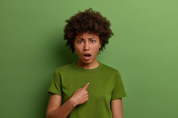 Mulher afro-americana assustada parece questionada e confusa de descrença, chocada por ser escolhida ou acusada de alguma coisa, mantém a boca bem aberta, vestida casualmente, parede verde brilhante.