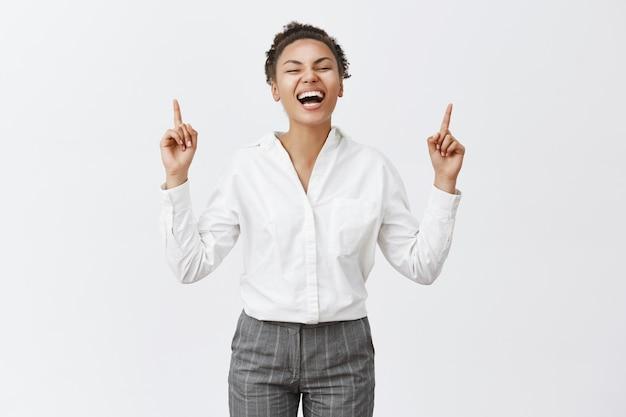 Mulher afro-americana atraente a apontar os dedos para cima e a sorrir
