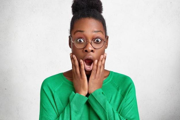 Mulher afro-americana atraente e emocional parece muito surpresa com a câmera, mantendo a boca bem aberta