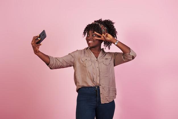 Mulher afro-americana atraente em roupas casuais leva selfie e mostra gesto com dois dedos no fundo rosa no estúdio