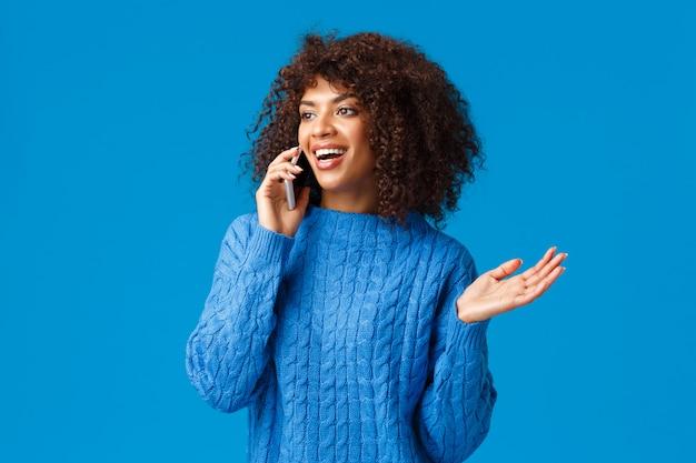 Mulher afro-americana atraente falante despreocupada na camisola de inverno discutir férias recentes e sua viagem ao exterior de esqui, falando no telefone, segurando o smartphone perto da orelha gesticulando, sorrindo