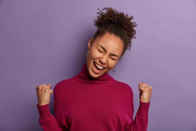 Mulher afro-americana bem-sucedida e eufórica comemora notícias incríveis, tem sorte de ganhar muito dinheiro, triunfa como um sonho tornado realidade, inclina a cabeça, vestida com gola olímpica casual, isolada na parede roxa