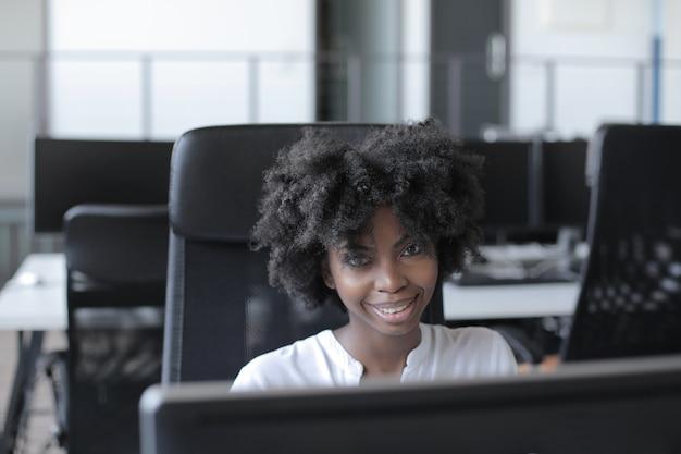 Mulher afro-americana bem-sucedida sentada em frente a um computador, trabalhando em um escritório moderno