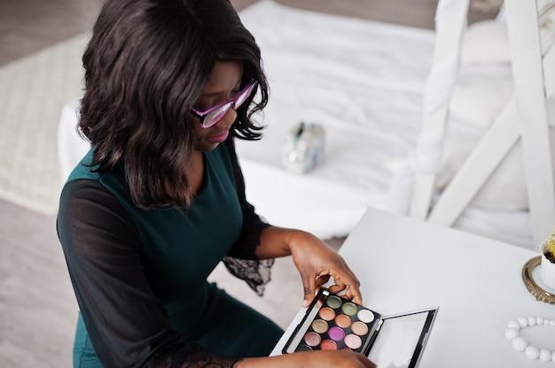 Mulher afro-americana bonita com maquiagem paleta nas mãos.